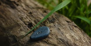 La pequeña roca con la escritura de 2 en ella colocó en rama de madera imagen de archivo libre de regalías