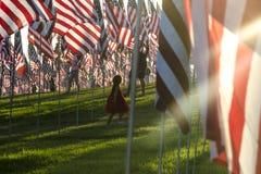 La pequeños muchacha y E.E.U.U. señalan el monumento por medio de una bandera del 11 de septiembre en Malibu Imagen de archivo