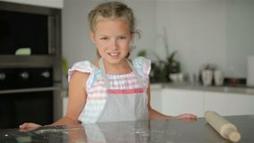 La peque?a muchacha linda est? cocinando en cocina Divertirse mientras que hace las tortas y las galletas Sonriendo y mirando la  metrajes