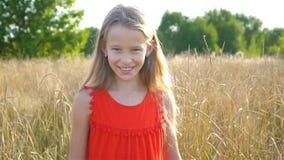 La peque?a muchacha rubia hermosa, tiene cara sonriente alegre de la diversi?n feliz, vestido rojo almacen de metraje de vídeo