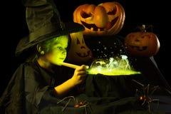 La pequeña bruja cocina una poción mágica en Halloween Imágenes de archivo libres de regalías