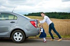 La pequeña hija ayuda a la madre joven a empujar un coche Foto de archivo libre de regalías