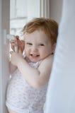 La pequeña muchacha astuta intenta abrir una ventana Imagenes de archivo
