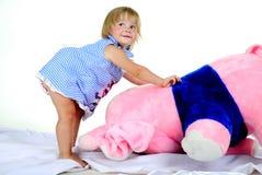 La pequeña muchacha con el elefante rosado grande Imagenes de archivo