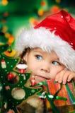 La pequeña muchacha feliz en el sombrero de santa tiene una Navidad Imágenes de archivo libres de regalías