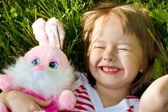 La pequeña muchacha feliz miente en hierba Fotografía de archivo