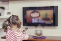 La pequeña muchacha linda con el telecontrol cambia el canal en la TV Fotografía de archivo libre de regalías