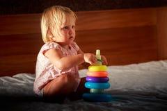 la pequeña muchacha rubia en rosa juega la pirámide en el sofá Foto de archivo libre de regalías