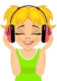 La pequeña muchacha rubia linda goza el escuchar la música con los auriculares Imagen de archivo