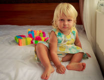 la pequeña muchacha rubia se sienta por la ventana en el sofá Imagen de archivo