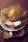 La pera caramellata ha immerso con le arachidi decorate con permesso dorato Immagini Stock