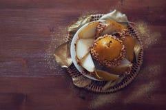 La pera caramellata ha immerso con le arachidi decorate con permesso dorato Fotografia Stock