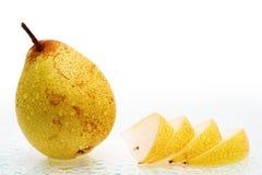 La pera fresca fruttifica con le fette e le gocce dell'acqua. Immagine Stock