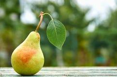 La pera verde con le foglie su marrone verde di legno ha invecchiato la fine del fondo di struttura su Pera sul fondo vago della  Fotografia Stock Libera da Diritti