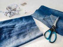 La pernera del pantalón con un agujero grande cortado con las tijeras del los tejanos dobló por la mitad Fabricación de pantalone fotos de archivo