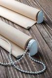 La persiana rodada del beige está en una superficie de madera Fotografía de archivo