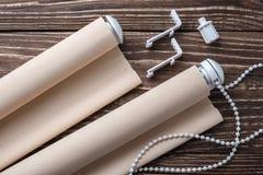 La persiana rodada del beige está en una superficie de madera Fotografía de archivo libre de regalías