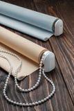La persiana rodada del beige está en una superficie de madera Foto de archivo libre de regalías