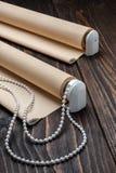 La persiana rodada del beige está en una superficie de madera Imágenes de archivo libres de regalías