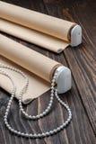 La persiana rodada del beige está en una superficie de madera Fotos de archivo
