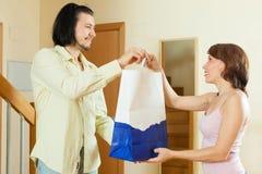 La persona abundante da un regalo a las mujeres en casa imágenes de archivo libres de regalías