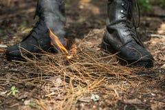 La persona accende il fuoco nella foresta Immagine Stock