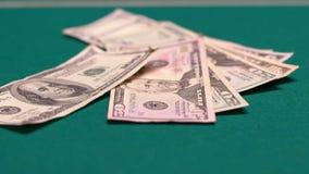 La persona atrevida que lanza la suma grande de dólares en la tabla de juego, dinero grande apuesta almacen de video