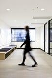 La persona borrosa pasa la sala de espera moderna Fotografía de archivo
