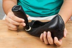 La persona che lucida e che ristabilisce consumata calza con la scarpa liquida po Immagine Stock Libera da Diritti