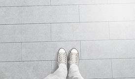 La persona che prende la foto del suo paga il supporto sul pavimento in bianco Fotografia Stock Libera da Diritti