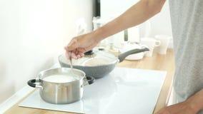 La persona cocina las gachas de avena de la harina de avena en cacerola metrajes