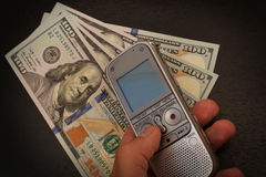 La persona cogió con operaciones del dinero alguien con un dictaphon Imagen de archivo libre de regalías