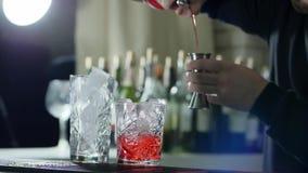La persona con la bottiglia nelle armi misura la proporzione di liquore in jigger e la versa in vetro con ghiaccio nella barra video d archivio