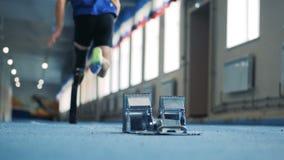 La persona con los soportes biónicos de la prótesis en una actitud y comienza a correr, opinión de la parte posterior almacen de metraje de vídeo