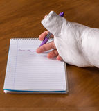 La persona con un brazo echó la escritura de una nota Fotografía de archivo libre de regalías