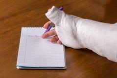 La persona con un brazo echó la escritura de una nota Foto de archivo libre de regalías