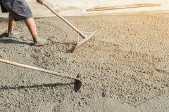 La persona de los trabajadores que no lleva la suciedad patea la excavación con la azada y x28; shovel& x29; imágenes de archivo libres de regalías