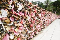 La persona degli amanti che mostra l'amore dalla chiave primaria di uso fissa la rete d'acciaio a Immagini Stock Libere da Diritti