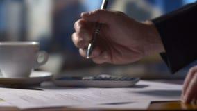 La persona del negocio del contable que trabaja en la declaración de impuestos forma en el escritorio en la calculadora almacen de metraje de vídeo