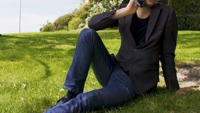 La persona del negocio que se sienta en césped en parque y que habla en el smartphone, urbano se relaja almacen de video