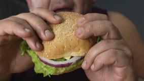 La persona di sesso maschile di peso eccessivo dubita per mangiare l'hamburger o non, decisione sana di vita stock footage