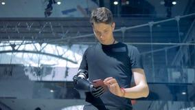 La persona discapacitada con un brazo del cyborg mecanografía adentro su teléfono, mirándolo 4K metrajes