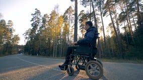 La persona discapacitada en una silla de ruedas accionada comienza a moverse almacen de metraje de vídeo