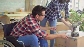 La persona discapacitada en una silla de ruedas recoge un nightstand en un nuevo apartamento moderno al lado de su esposa almacen de metraje de vídeo