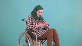La persona discapacitada musulmán joven de la mujer en una silla de ruedas utiliza el teléfono en un fondo azul metrajes