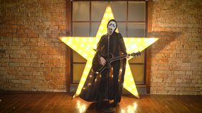 La persona en guitarra de los juegos de la máscara del grito, canta en el micrófono, estrella estupenda, danzas, el hacer muecas, almacen de video