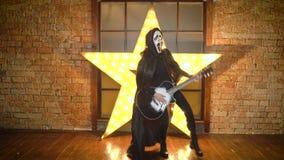 La persona en la guitarra de los juegos de la máscara del grito, estrella estupenda, danzas, el hacer muecas, engañando alrededor almacen de video