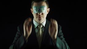 La persona en un traje cierra ojos por el billete de banco del ciento-dólar metrajes