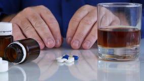 La persona enviciada con la sacudida de las manos toma el medicamento de la tabla con alcohol almacen de metraje de vídeo