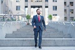 La persona feliz del negocio camina abajo en el movimiento de la prisa con la tableta Hombre de negocios contemporáneo joven que  foto de archivo libre de regalías